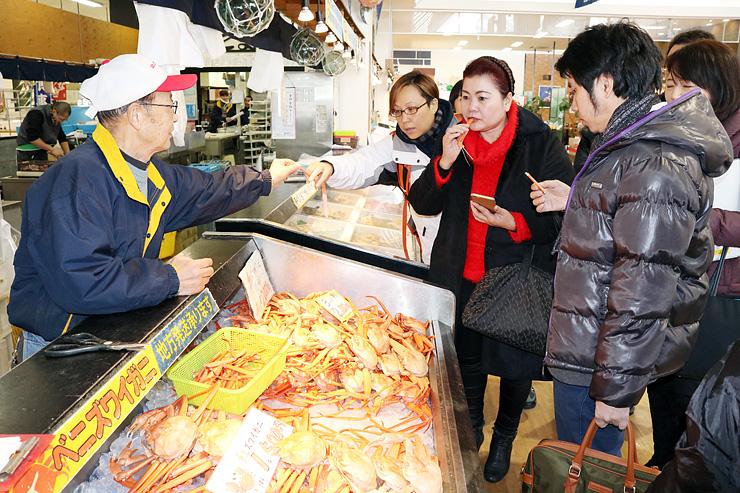 ベニズワイガニを試食するタイと香港の食品卸売業者幹部=新湊きっときと市場