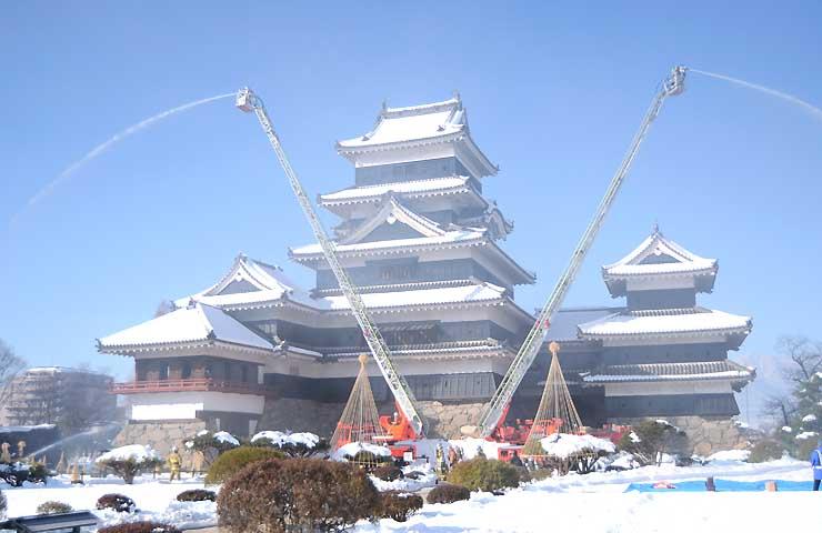 はしご車で一斉放水した消防総合訓練=26日、松本市の松本城