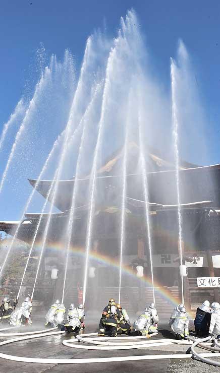 善光寺本堂に向けて行われた一斉放水訓練=26日、長野市