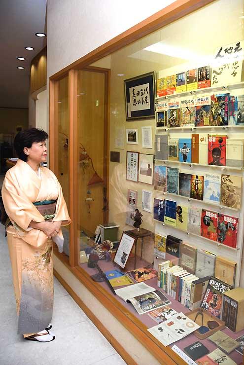 展示された火坂さんの著書などを眺める久保さん