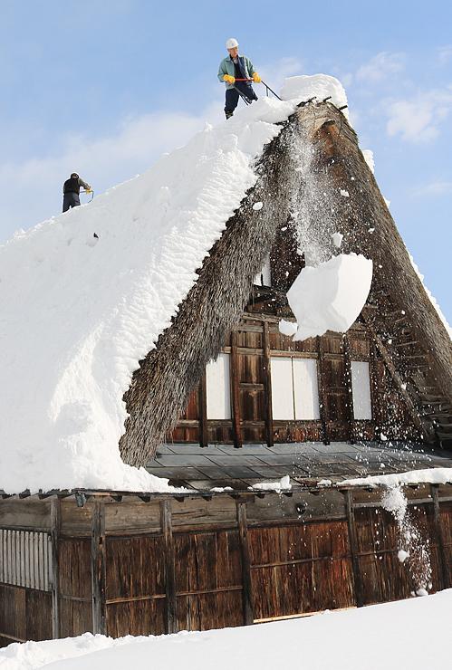 青空の下で行われた合掌造り家屋の屋根雪下ろし=南砺市相倉