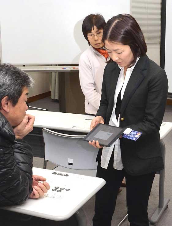タブレット端末を使い、モバイル決済を実演するスクエアの社員