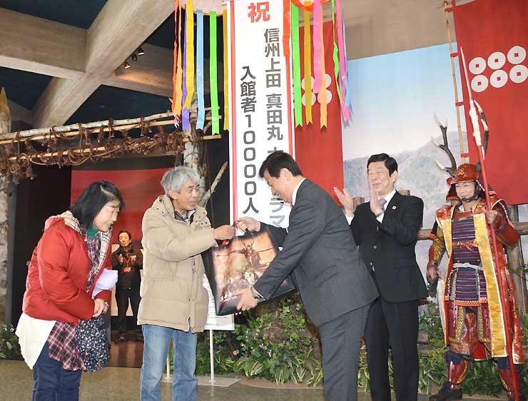 大河ドラマ館の入館1万人目となり、記念品を受け取る久保田さん夫妻(左の2人)