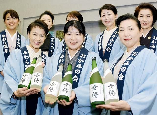 完成した本年度の「女将」を手にする女将=28日、福井県あわら市の芦原温泉旅館会館