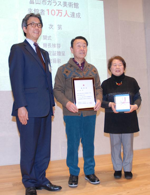 渋谷館長(左)から来館10万人目の認定証を贈られた秋元さん(中央)と妻の千枝子さん