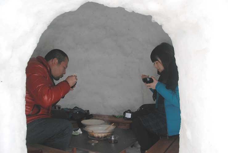 かまくら内で鍋を楽しむ観光客