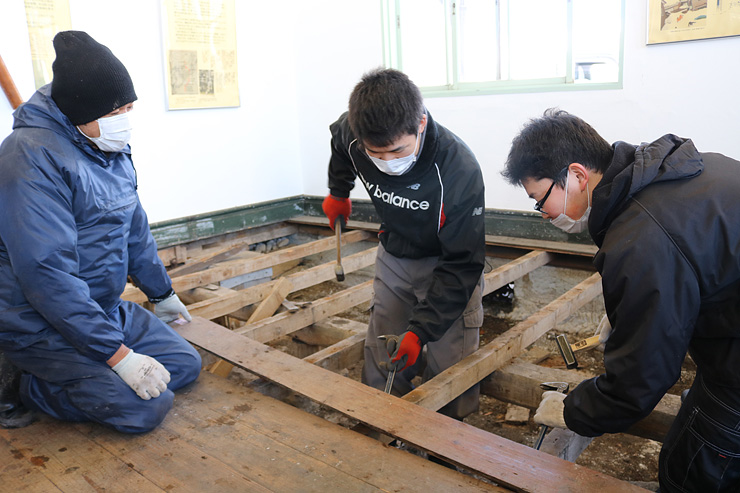 若松代表(左)と一緒に床板を剥がす生徒=高岡市伏木気象資料館