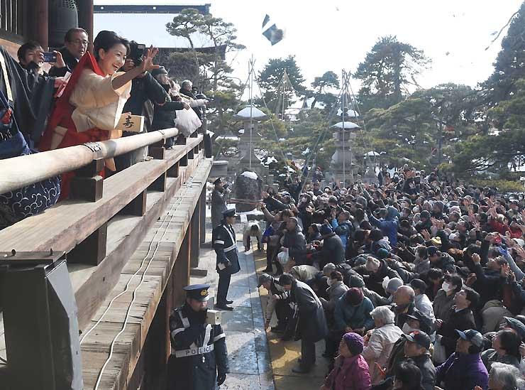 大勢の老若男女に向かって「福」をまく特別ゲストの羽田美智子さんら=3日午後2時2分、長野市の善光寺本堂