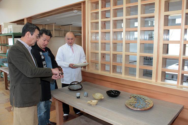 厨房室(右奥)が設けられた陶農館で、器を見ながら打ち合わせる(左から)釈永さん、犬島さん、中尾さん
