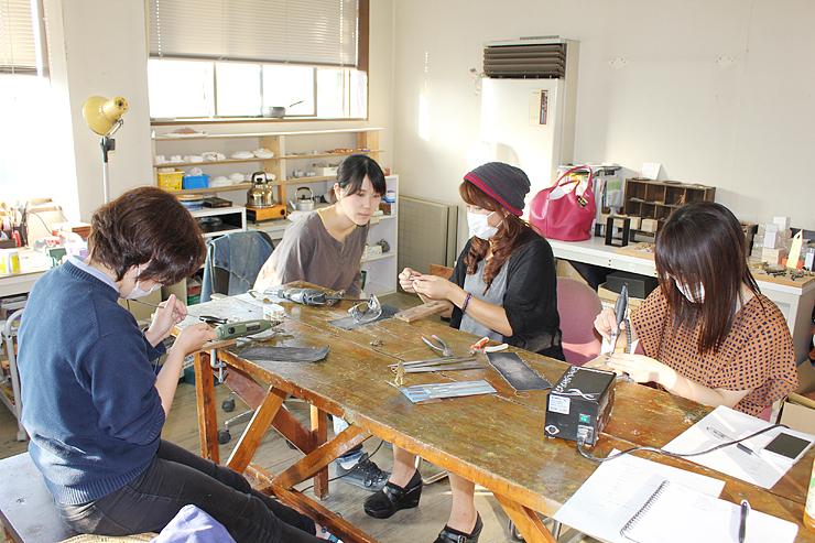 仕事旅行社が企画したものづくり体験ツアーで鋳物の仕上げに取り組む参加者=2014年10月、高岡市内