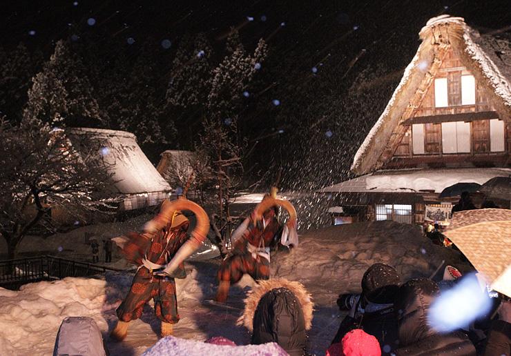 雪が降りしきる中、ライトアップされた合掌造り家屋を背景にささら踊りを披露する踊り手=南砺市菅沼