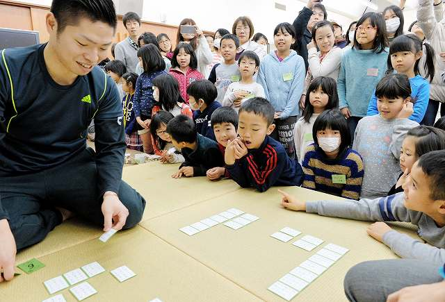子どもたちの前で競技かるたを実演する川崎文義名人(左)=7日、福井県立こども歴史文化館
