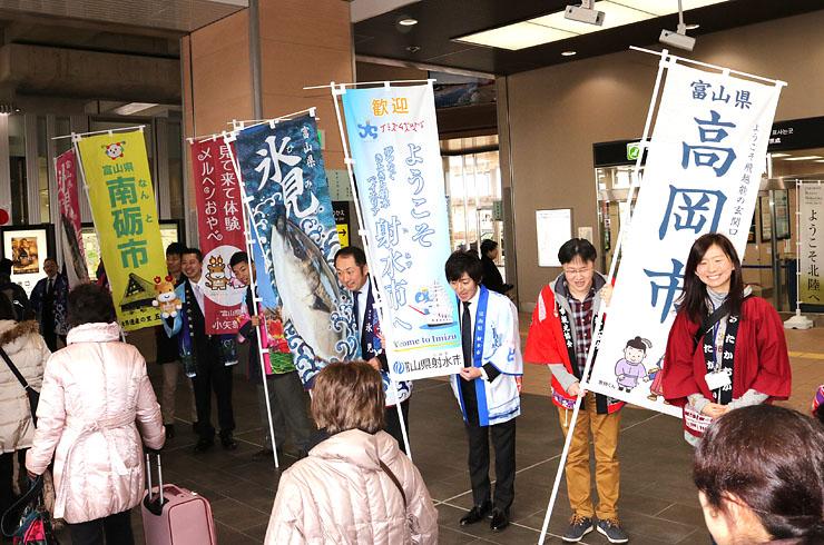 のぼり旗を手にツアー参加者を出迎える県西部6市の職員=JR新高岡駅