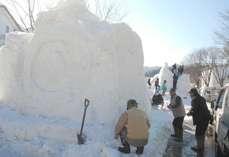 SL(左)や飯山市文化交流館などを表現した雪像造りが進む「いいやま雪まつり」会場