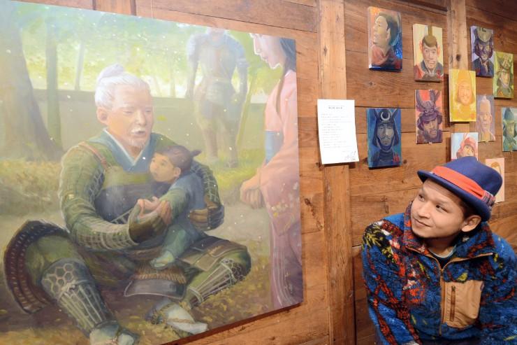 真田昌幸と小松姫の逸話を題材にしたアクリル画などが並ぶ鶴田さん(右)の個展