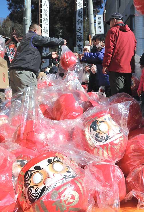鉾持神社参道でだるまを売り買いする人たち
