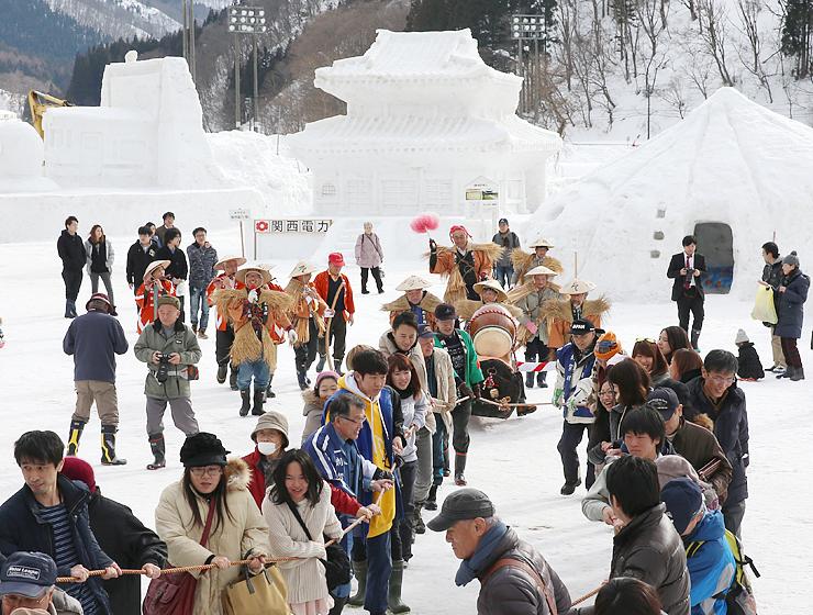 雪像が並ぶ会場で、来場者も参加して行われた伝統の「丑曳き」=利賀国際キャンプ場
