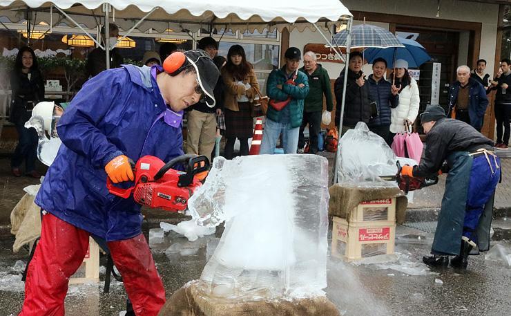 大勢の来場者が見守る中、チェーンソーで作られる「氷の彫刻」=いなみ木彫りの里