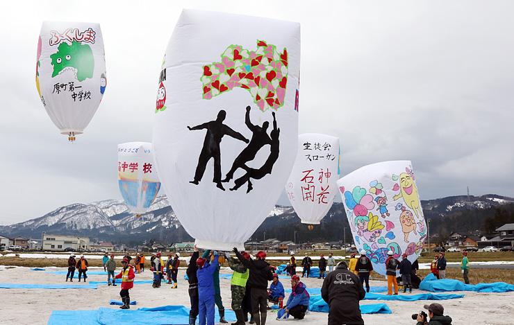 医王山を背景に冬空に浮かぶ巨大紙風船。南相馬市の生徒が絵を描いた4基も揚がった=南砺市中ノ江