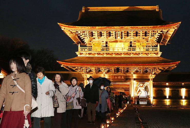 厳かに照らされた山門前を歩く大勢の人たち=瑞龍寺