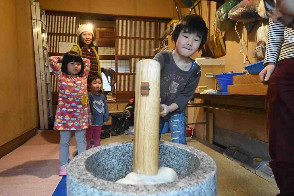 餅つきを楽しむ参加者たち=14日、福井県鯖江市河和田町の「かわだ尾花屋まちライブラリー」