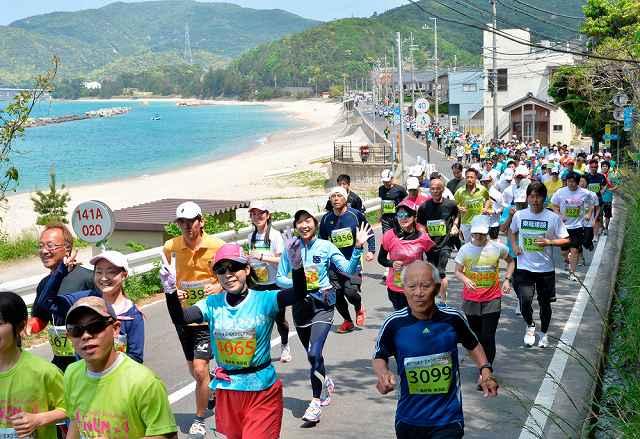 昨年の第27回美浜・五木ひろしマラソン大会で、潮風を受け海岸沿いのコースを駆け抜けるランナー=2015年5月、福井県美浜町竹波