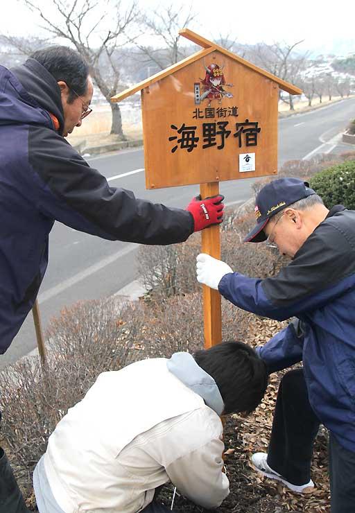 海野宿付近に真田信繁のキャラクターがデザインされた案内板を立てる海野宿保存会員ら