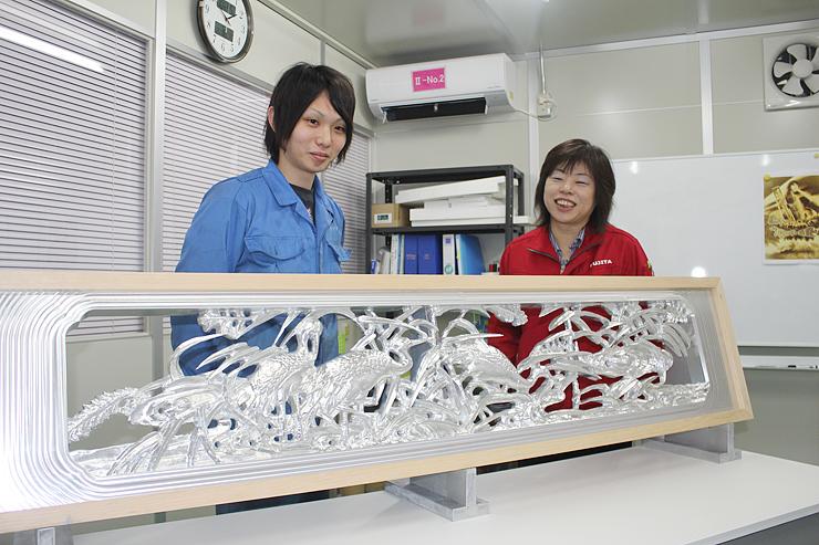 メタルアートミュージアム開設に向けて、アルミの欄間作品などの準備を進める梶川社長(右)=高岡市福岡町荒屋敷のフジタ第2工場