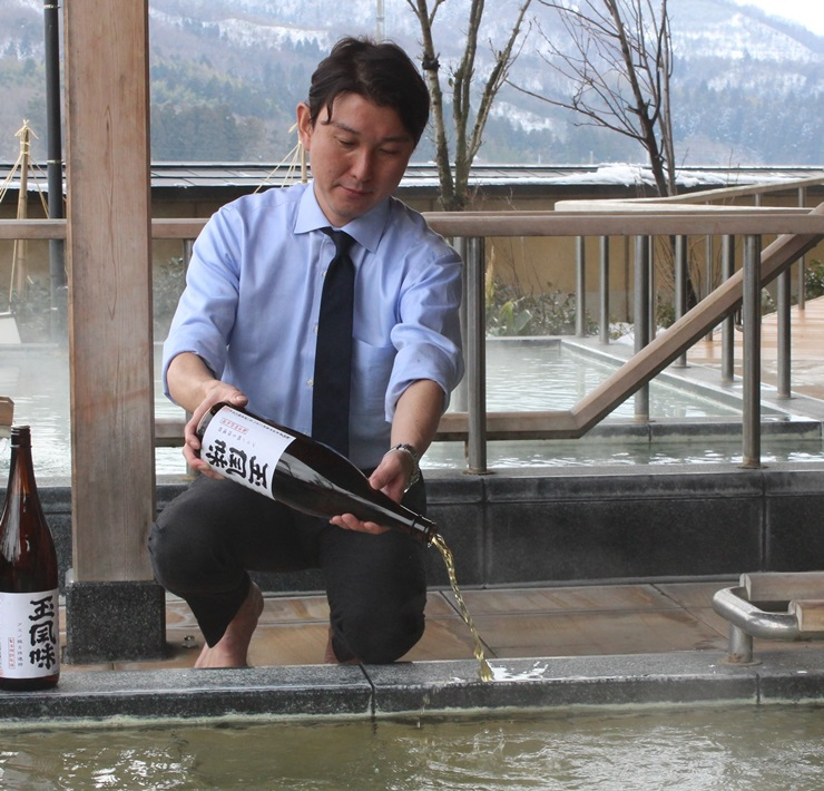 風呂専用の日本酒「湯悦燗」を注ぐ県旅館ホテル組合青年部のメンバー。ラベル完成前で、別銘柄の一升瓶に入れて注いだ=新発田市月岡温泉の華鳳
