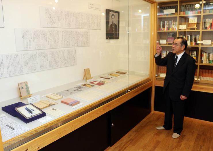 三島の創作の軌跡を著書などから説明する杉田館長=富山市向新庄町の「隠し文学館 花ざかりの森」