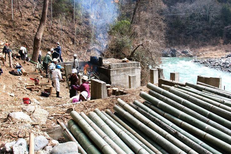 天竜川沿いの竹林で伐採した竹を積み上げるプロジェクト参加者たち。一面竹やぶだった川沿いに光が差すようになった=27日、飯田市
