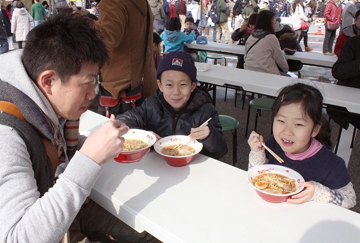 さまざまな種類のラーメンを味わう来場者=入善町入膳のうるおい館前特設会場