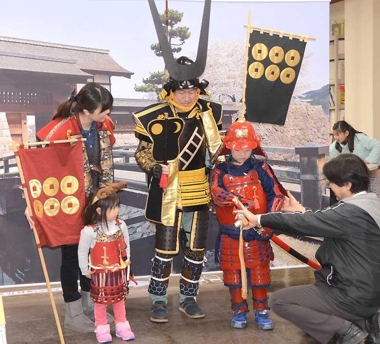 真田昌幸の甲冑の複製(中央)を着て記念撮影の準備をする親子