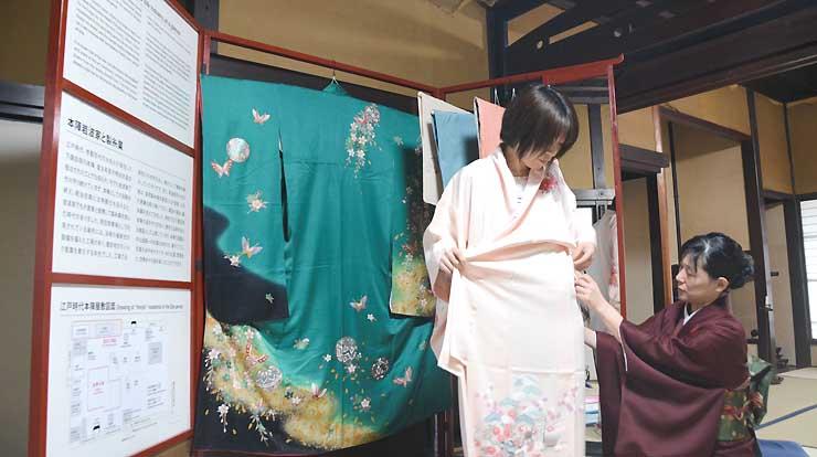 衣桁を模した英訳付き案内板と着物掛けを背に試着できる本陣岩波家