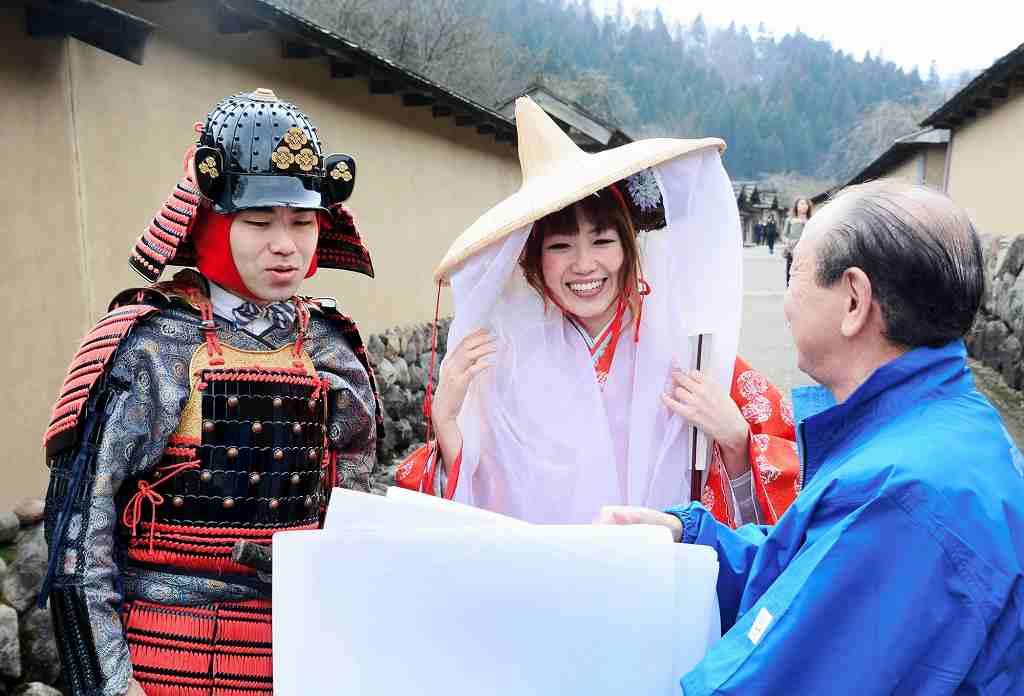 戦国衣装に身を包み、遺跡の説明に耳を傾けるムコさん(左)とアンジーさん(中央)=6日、福井市の一乗谷朝倉氏遺跡復原町並