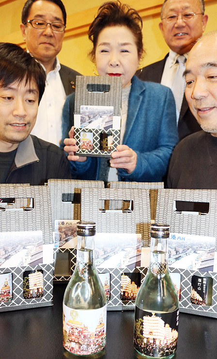 完成した「新湊曳山まつり地酒セット」を見て笑顔の朴木組合長(奥右)ら組合員=錦松亭