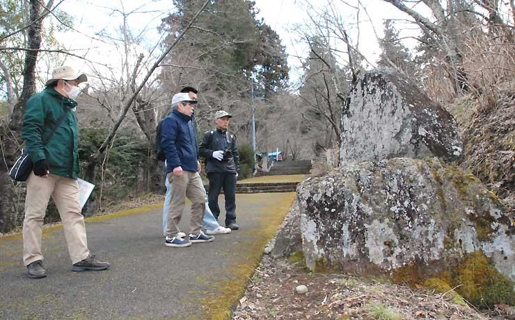 如法寺の参道脇にある松尾芭蕉の句碑を眺める会員ら