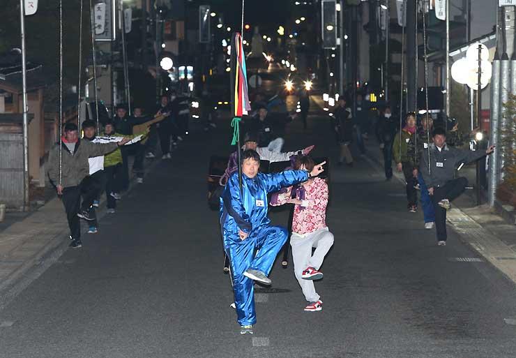 飯田市本町3の路上で真剣な表情で練習に励む大名行列の役者たち=11日夜