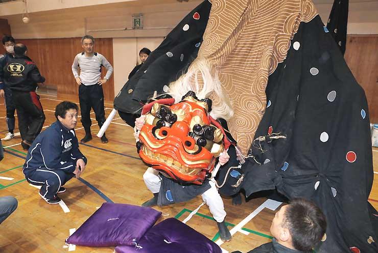飯田東中学校の体育館で獅子頭を使って練習する東野大獅子の保存会員たち=10日夜