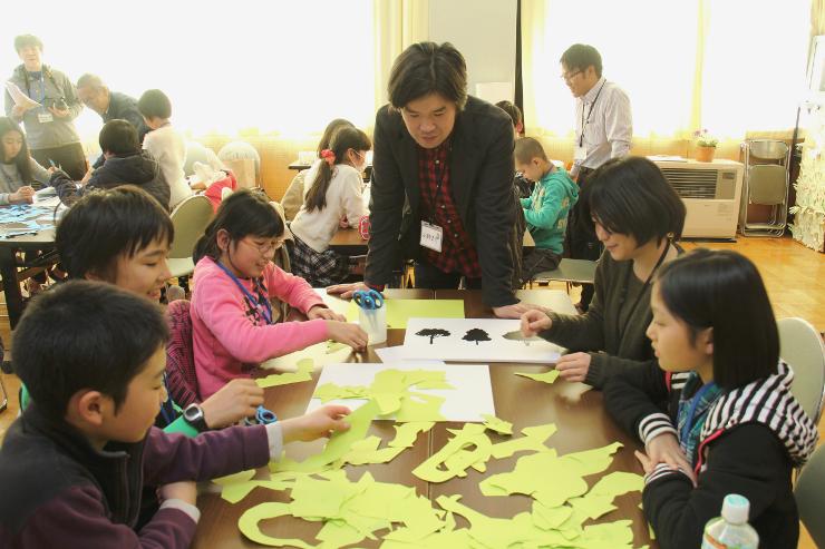 小野さん(中央)の助言を受けてシンボルマークを考える小学生たち