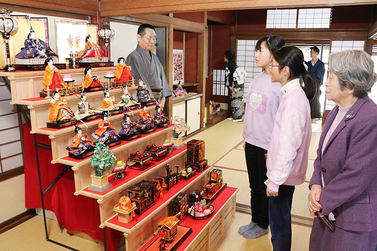 きらびやかなひな人形に見入る来場者=高岡市土蔵造りのまち資料館
