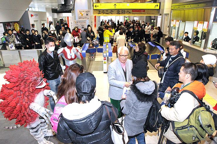 ウルトラマンや怪獣と一緒に乗客を出迎える黒部進さん(中央)=黒部宇奈月温泉駅