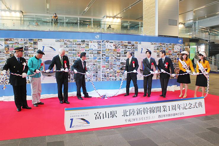 新幹線開業1年の記念式典で、写真パネルを除幕する出席者=富山駅