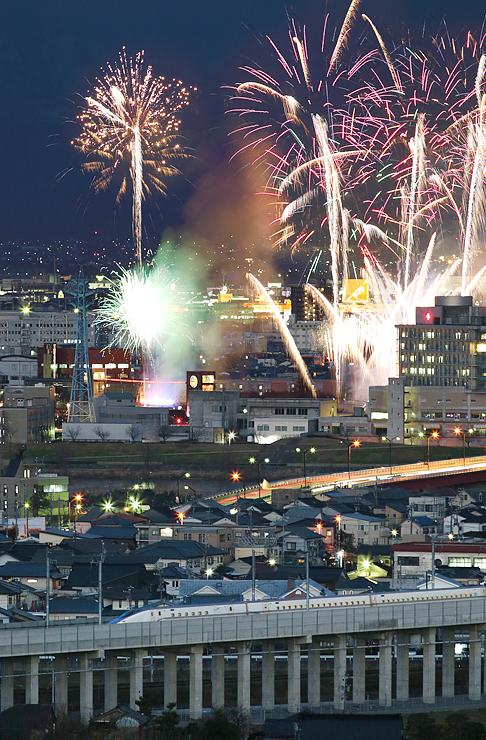 夜の富山市内を走る北陸新幹線と開業1周年を記念した大輪の花火=呉羽山から(新幹線と花火を同一構図で別々に撮影し合成、写真部部長デスク・垣地信治撮影)