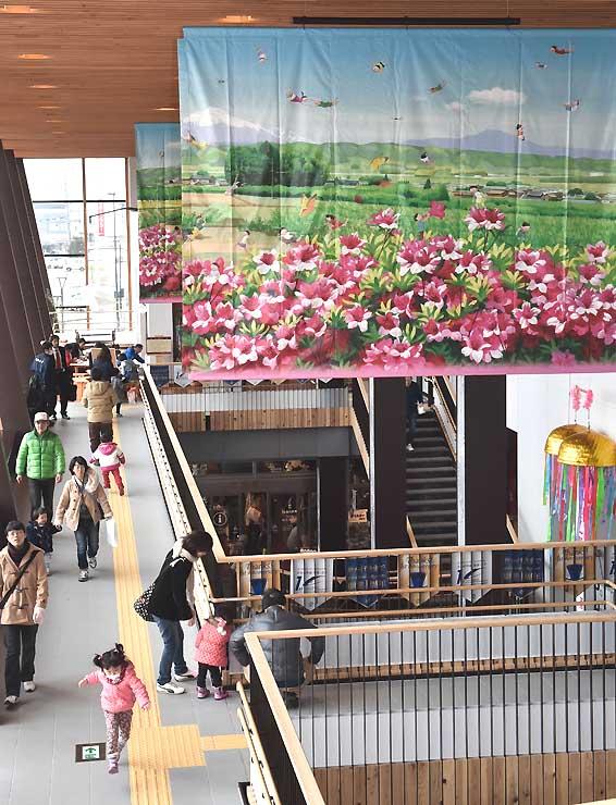 記念イベントでお披露目された藤岡牧夫さんの作品「五岳の風」(右上)=13日、飯山市の飯山駅観光交流センター