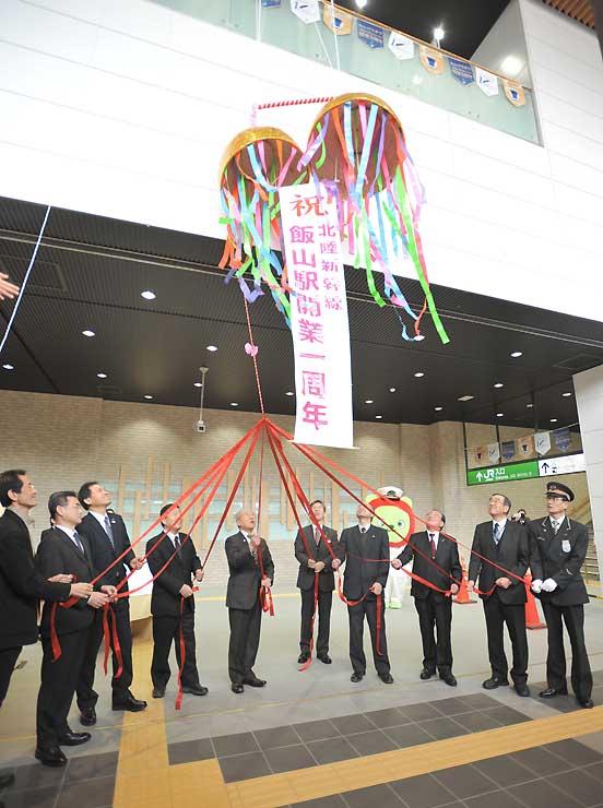 開業1周年を祝ってくす玉を割る関係者=飯山駅
