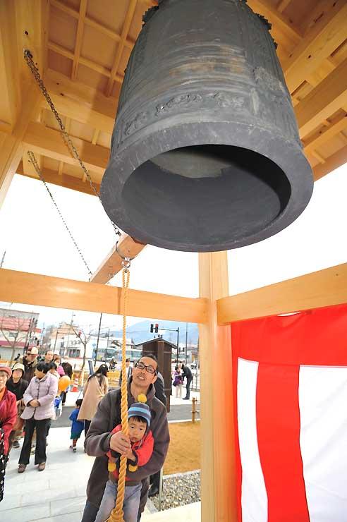 旧飯山駅ホームから移設された「七福の鐘」。家族連れらが「お撞(つ)き初め」をした=雪と寺の町シンボル広場