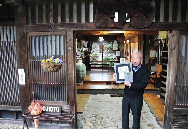 藤乙の玄関前で、贈られた盾を手にする藤原洋平社長