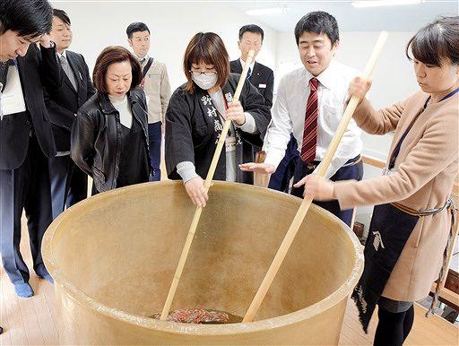 しょうゆ造りの作業の一つ、櫂入れについて説明する野村社長(右から2人目)=16日、福井県大野市