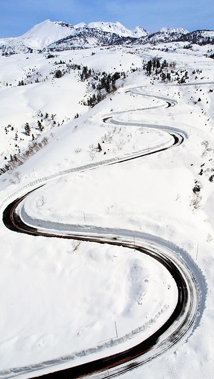 除雪が進み、立山・七曲付近の雪原に現れた高原バス道路の曲線=16日午前11時43分